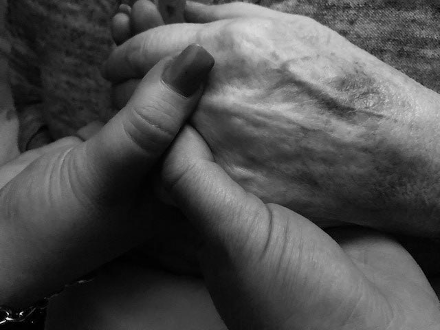 a younger and older hand holding each other tenderly